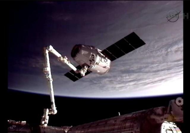 Braço robótico Canadarm2, da ISS, captura a Dragon.