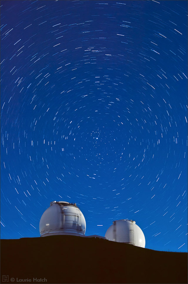 Spherical domes of the twin 10-meter telescopes are illuminated by the rising moon in this 15 minute time exposure.
