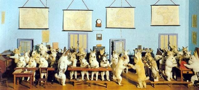 """Uma foto de 1930 que mostra o diorama """"Escola de Coelhos"""", de Walter Potter. Potter foi um taxidermista amador que viveu em meados dos anos 1800 e criou dioramas de animais fazendo atividades humanas. (Via Wikipedia, licença Creative Commons)"""