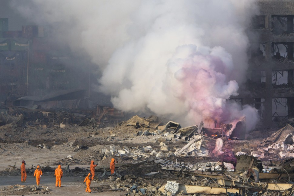 Fire fighters in protective gear watch partially pink smoke continue to billow after an explosion at a warehouse in northeastern China's Tianjin municipality, Thursday, Aug. 13, 2015. Huge, fiery blasts at a warehouse for hazardous chemicals killed many people and turned nearby buildings into skeletal shells in the Chinese port of Tianjin, raising questions Thursday about whether the materials had been properly stored. (AP Photo/Ng Han Guan)