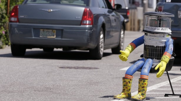 A car drives by HitchBOT, a hitchhiking robot Friday, July 17, 2015, in Marblehead, Mass. HitchBOT is beginning its' first cross-country hitchhiking trip of the U.S., in Marblehead with a final destination goal of reaching San Francisco. (AP Photo/Stephan Savoia)
