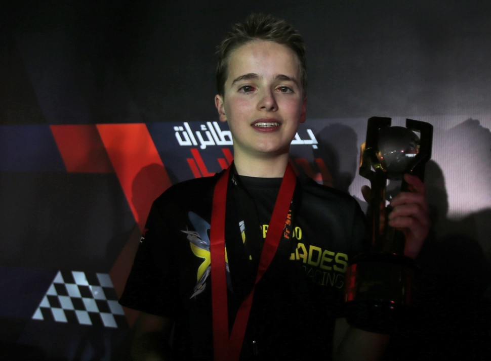 Luke Bannister of Somerset, a 15 year old British pilot of Bannister's team, Tornado X-Blades Banni UK, holds the trophy after he won the first World Drone Prix in Dubai, United Arab Emirates, Saturday, March 12, 2016. (AP Photo/Kamran Jebreili)