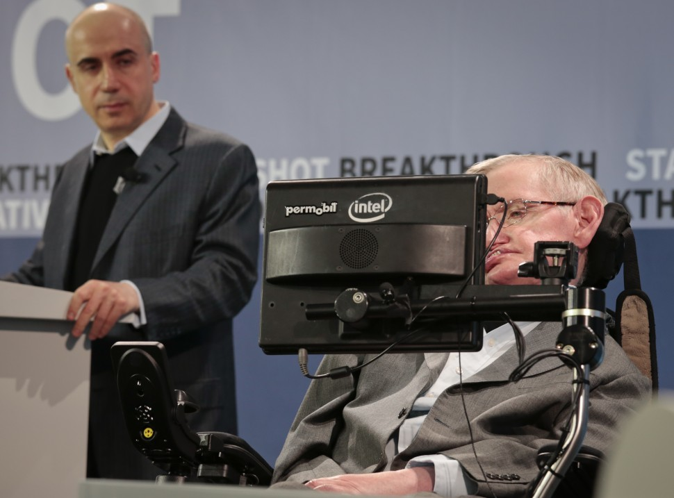 Internet investor and science philanthropist Yuri Milner, left, listens as renowned cosmologist Stephen Hawking, right, speaks with the assistance of adaptive speech technology, during a press conference announcing the new Breakthrough Initiative focusing on space exploration and the search for life in the universe, Tuesday April 12, 2016, at One World Observatory in New York. The $100 million project is aimed at establishing the feasibility of sending a swarm of tiny spacecraft, each weighing far less than an ounce, to the Alpha Centauri star system. (AP Photo/Bebeto Matthews)