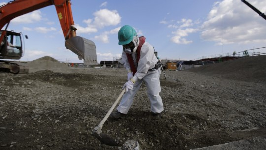 A worker, wearing a protective suit and a mask, levels ground at the tsunami-crippled Fukushima Dai-ichi nuclear power plant, operated by Tokyo Electric Power Co. (TEPCO), in Okuma, Fukushima Prefecture, northeastern Japan, Wednesday, Feb. 10, 2016. In one month, Japan is marking the fifth anniversary of a devastating earthquake and tsunami that hit on March 11, 2011 and left nearly 19,000 people dead or missing, turned coastal communities into wasteland and triggered a nuclear crisis. (Toru Hanai/Pool Photo via AP)