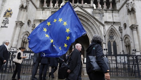 A Pro-EU membership supporter walks with a EU flag outside the High Court, on the second day of the lawsuit of Gina Miller, a founder of investment management group SCM Private in London, Monday, Oct. 17, 2016. Rival protesters have gathered outside the High Court in London, where lawyers are battling over whether the government has the power to trigger Britain's exit from the European Union without approval from Parliament. (AP Photo/Frank Augstein)