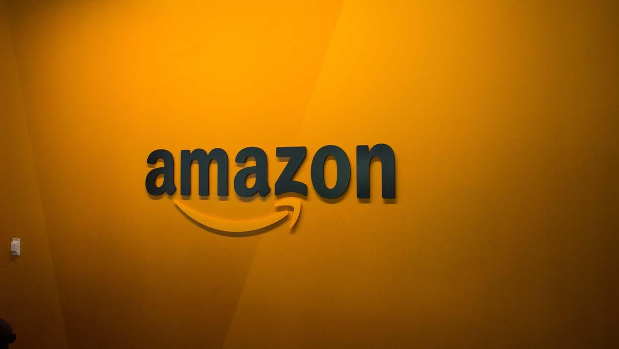 Logo da Amazon em uma parede amarela.