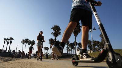 duas pessoas usam patinetes elétricos. só se vê as pernas da primeira pessoa na imagem. a segunda está mais distante da câmera. é um dia ensolarado, e há palmeiras ao fundo da imagem.