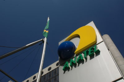 Fachada da Anatel. A cor predominante é prata, e o logo da Anatel é um círculo azul e uma curva em amarelo, com a palavra Anatel escrita em maiúsculas na cor verde. O dia está ensolarado e o céu, azul. Há uma bandeira do Brasil hasteada logo em frente ao prédio.