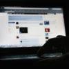 Homem em sala escura com o monitor do computador mostrando a página inicial da rede. Crédito: Dan Kitwood/Getty Images