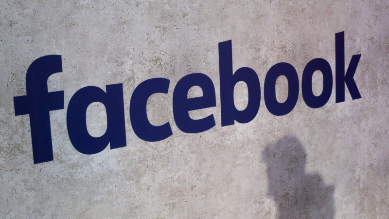 Logo do Facebook em azul sobre uma parede cinza