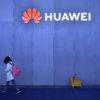 Pessoa caminha ao lado de logotipo da Huawei