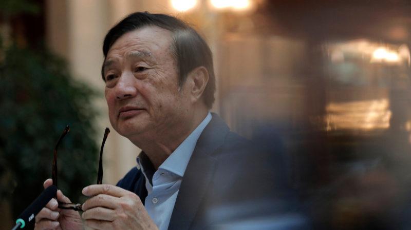Ren Zhengfei, um senhor asiático aparentando algo em torno de 70 anos de idade. Ele veste um blazer cinza e uma camisa azul claro e segura óculos escuros fora do seu rosto. Ele está levemente virado para a esquerda.