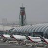 Foto do Aeroporto Internacional de Dubai. Há dois galpões e uma torre de controle ao fundo. Na frente, sete aeronaves da Fly Emirates está paradas, voltadas para os galpões.