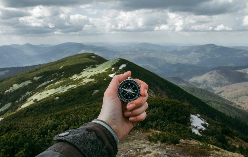 Uma mão esquerda segura uma bússola. O ponto de vista da foto é dessa pessoa segurando a bússola diante de si mesma. Ao fundo, montanhas e um céu cheio de nuvens.