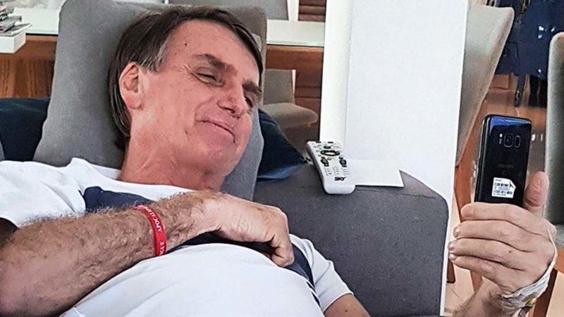 Jair Bolsonaro deitado e mexendo no celular