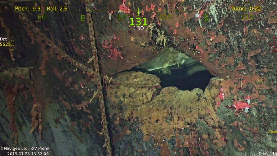 Imagem subaquática. O casco do navio está bastante deteriorado, com sinais de ferrugem. Há um buraco de cinco lados no casco.