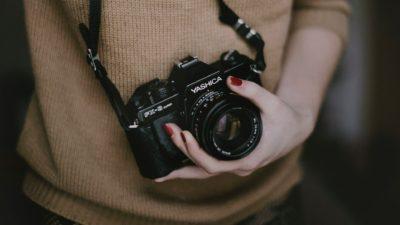 Foto de uma mulher com uma câmera pendurada no pescoço. O recorte deixa à mostra apenas a altura entre o peito e a barriga. A mão esquerda da mulher segura a câmera.