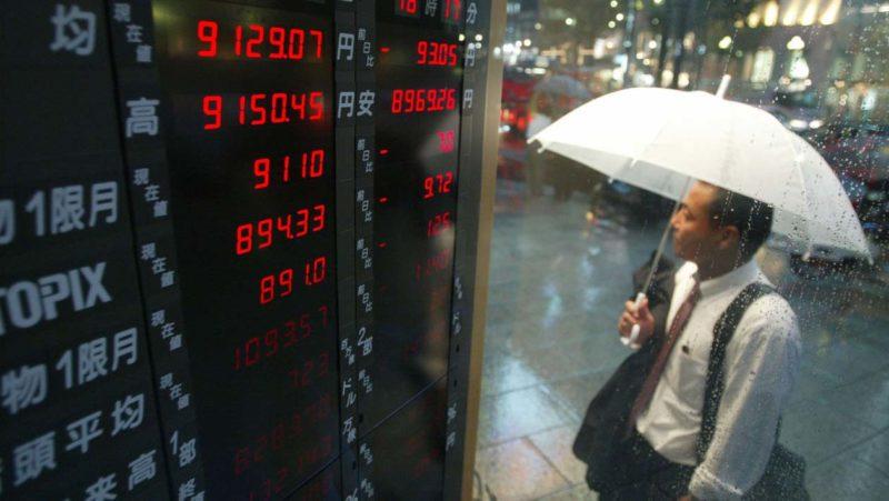 Homem olha preços de ações durante chuva em Tóquio, em 2002