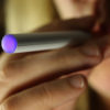 Imagem aproximada de uma pessoa fumando cigarro eletrônico