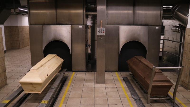 Crematório. Há duas câmaras para cremação -- buracos abertos em uma parede metálica. Em frente a cada um desses buracos, há um caixão.