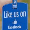 """Adesivo em estabelecimento com os dizeres """"Nos curte no Facebook"""", em inglês."""