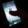 Celular no escuro com ícones de aplicativos WhatsApp e Facebook