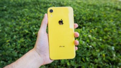 Apple iPhone XR amarelo na mão esquerda de uma pessoa. As costas do aparelho estão viradas para a câmera. Ao fundo, um gramado.