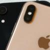 Dois iPhones, um preto e um dourado, empilhados, com a parte de trás virada para cima. O logo da Apple do iPhone dourado está à mostra.