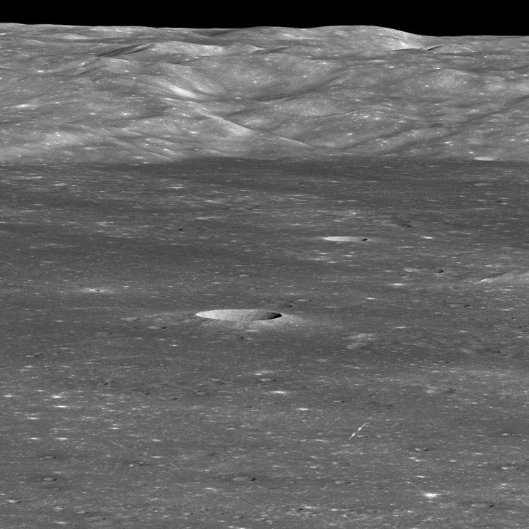 Imagem em preto e branco da superfície do lado oculto da Lua. Há uma cratera bem no centro da imagem e duas setas pequenas indicando um ponto minúsculo no canto inferior direito. Ao fundo, uma montanha, que é a parede da cratera.