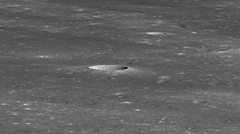 Imagem em preto e branco da superfície do lado oculto da Lua. Há uma cratera bem no centro da imagem e duas setas pequenas indicando um ponto minúsculo no canto inferior direito.
