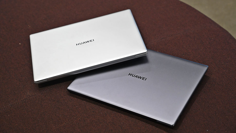Dois notebooks empilhados um sobre o outro, de maneira torta. Um é prata e outro é cinza escuro.