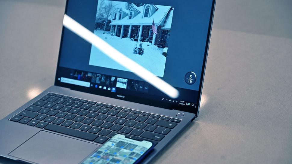 Notebook com um smartphone apoiado sobre ele. O notebook está aberto. Sua tela mostra uma imagem que está na galeria do smartphone.