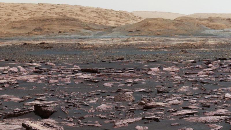 perspectiva do monte Sharp. o solo é escuro, rochoso e bastante pontiagudo. o monte, ao fundo, é de uma cor avermelhada, cresce de maneira bastante suave.