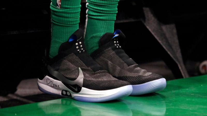 Foto dos pés do jogador de basquete Jayson Tatum. Eles estão vestindo meias verdes e calçando os tênis da Nike, que são pretos, com a sola branca, e sem cadarços. O chão da quadra também é verde, cor do Boston Celtics.
