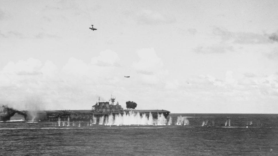 Foto mostra o porta-aviões sendo atacado no mar. Há água sendo levantada pelo impacto dos tiros. Dois aviões sobrevoam a região. Um deles está embicado para baixo e outro, em paralelo ao mar.