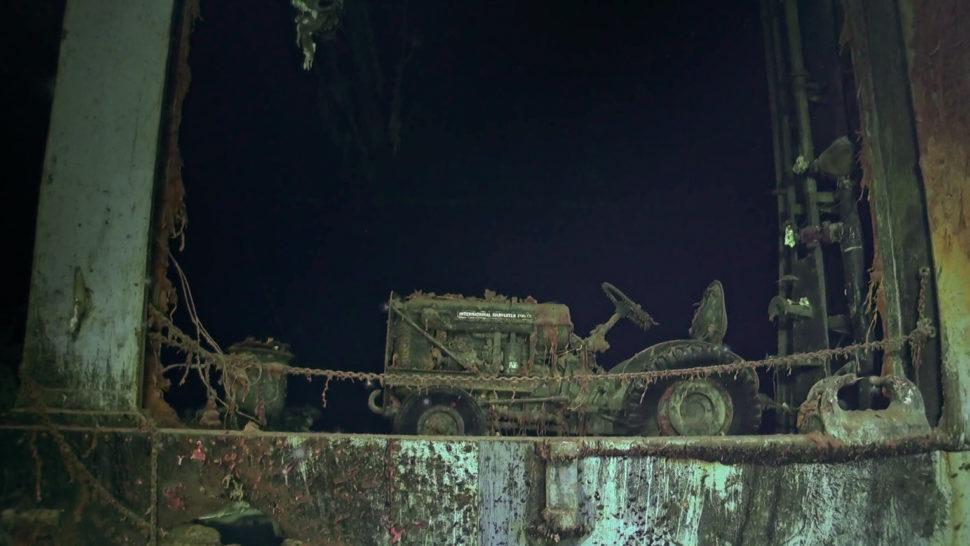 Um rebocador, veículo parecido com um trator, está no convés do porta-aviões nesta imagem subaquática.
