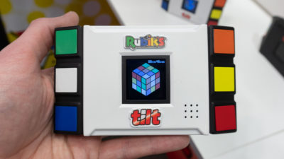 frente do minigame. ele é um pouco maior que a palma da mão que o segura na foto. ele é branco, retangular, e tem decorações coloridas nas laterais. no meio, uma pequena tela mostra um cubo mágico em 3d.