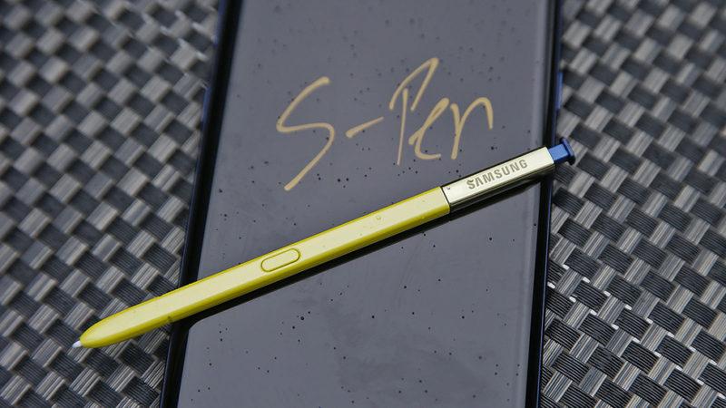 Foto de aparelho Galaxy Note 9, da Samsung, com sua caneta stylus apoiada sobre a tela. Na tela, está escrito S-Pen em amarelo sobre fundo preto.