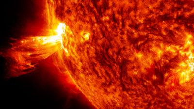 Representação artística em close do Sol, mostrando suas chamas, em cores preto e vermelho.