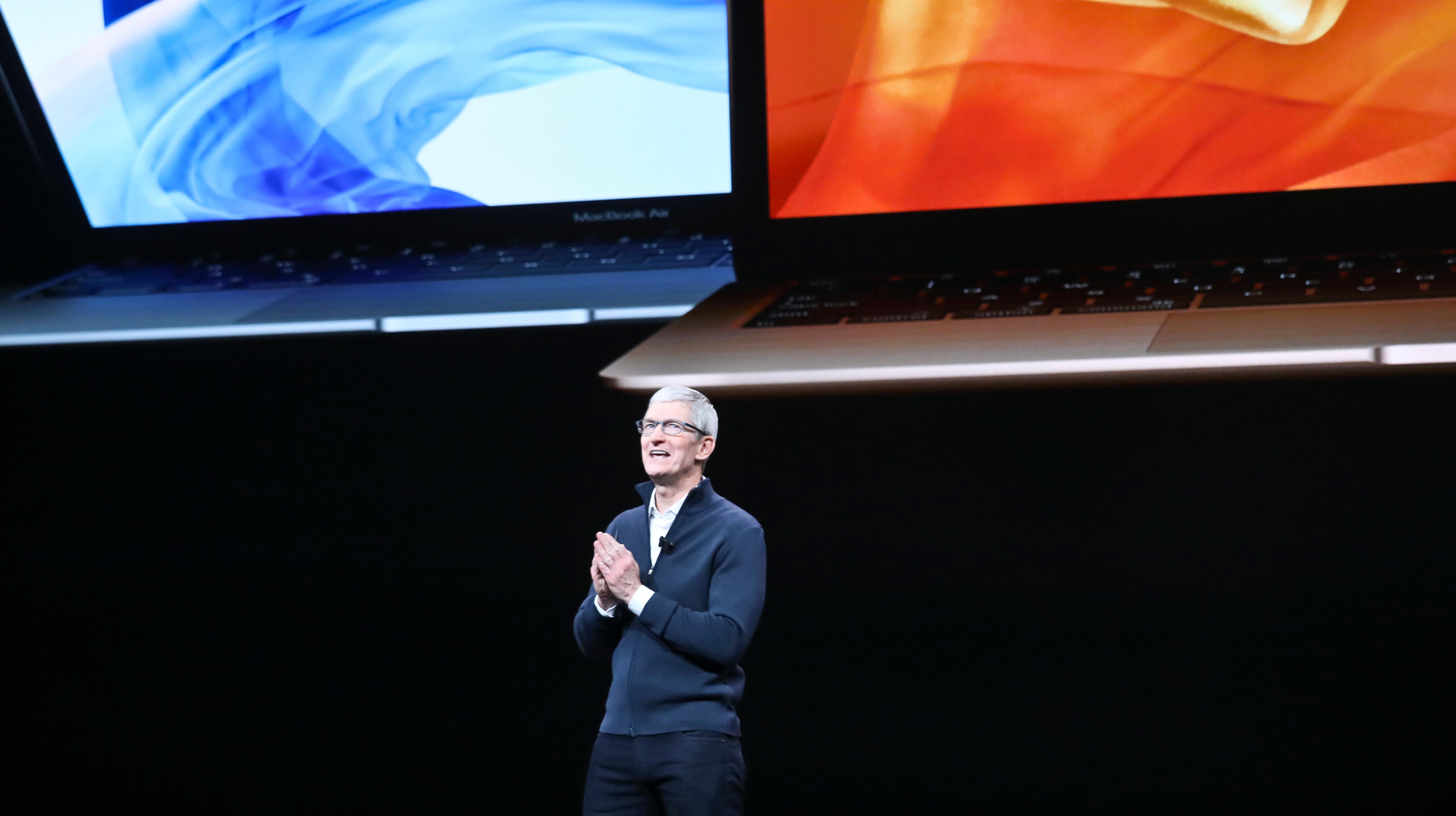 Tim Cook, CEO da Apple, em uma apresentação da empresa. Ao fundo, um telão mostra dois notebooks da marca.