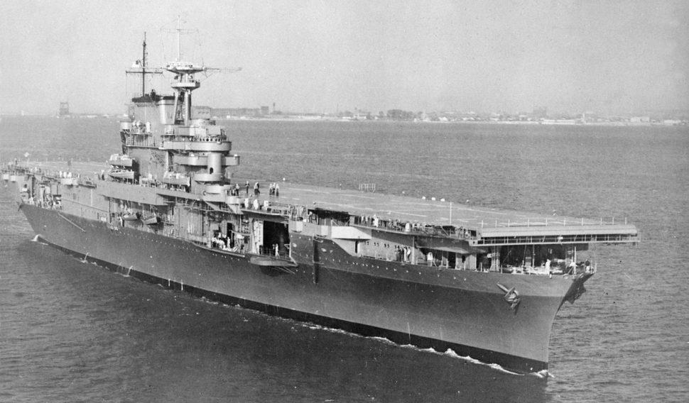 Fotografia em preto e branco do porta-aviões USS Hornet no mar. Ele está em diagonal. Há algumas pessoas no convés, e elas ficam muito pequenas perto do tamanho da embarcação.