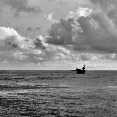 O porta-aviões USS Hornet no mar, visto de longe, um pouco inclinado.