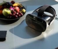 Mesa com o dispositivo Varjo VR-1, sua caixa de alimentação e uma tigela de frutas