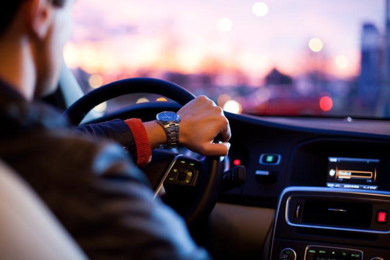 Imagem de motorista dirigindo carro. O ponto de vista é do passageiro do banco traseiro. O motorista tem uma das mãos no volante, e a outra abaixada. Pelo para-brisa, dá para ver o entardecer.