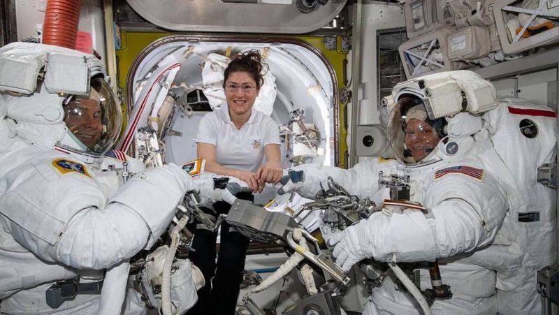 Astronauta Christina Koch (centro) ajuda os colegas Nick Hague (esquerda) e Anne McClain na Estação Espacial Internacional