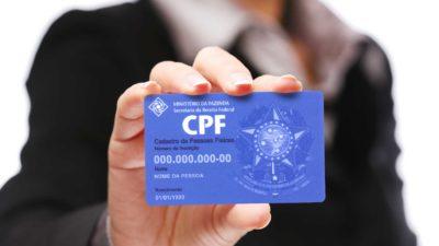 Mulher segura um CPF (cadastro de pessoa física) sem números válidos