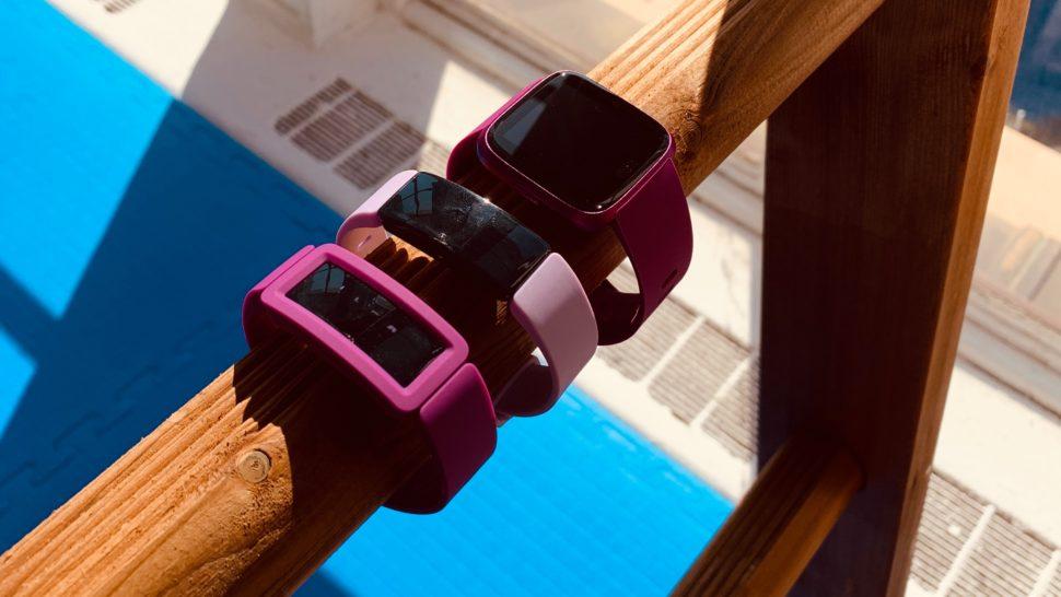 Uma pulseira rosa, uma pulseira branca e um smartwatch roxo em um suporte de madeira.