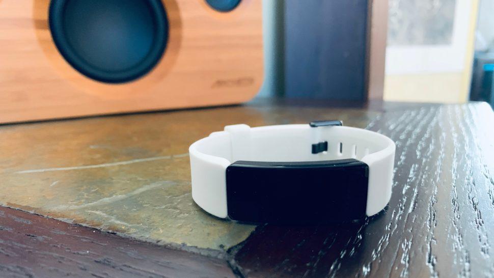 Uma pulseira branca com aparelho preto sobre um chão de madeira.