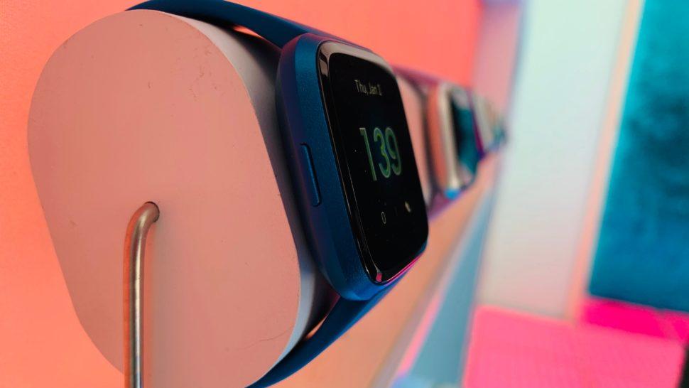 """Um smartwatch azul visto pela lateral. Na tela dele, está escrito """"139"""", possivelmente significando batimentos cardíacos. Ao fundo, mais relógios."""