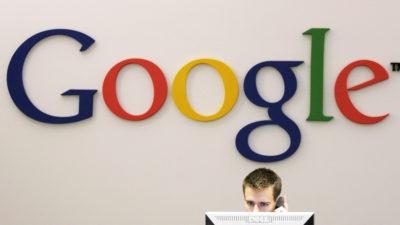 parede de escritório com o logo do Google. há um funcionário trabalhando em frente a ela. a parte superior da cabeça do funcionário está visível por trás de um monitor.